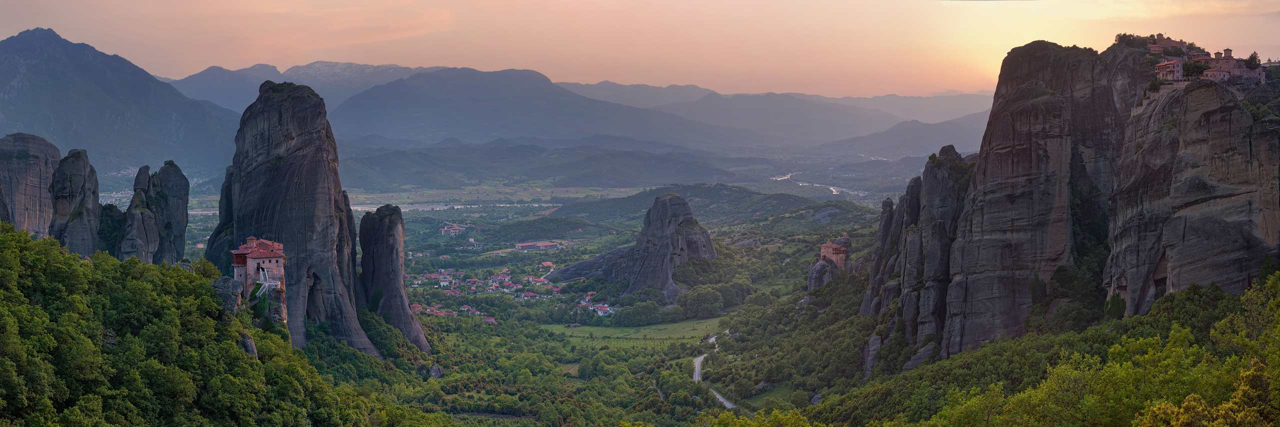 Roussanou and St. Nicholas Anapafsas Monasteries with town of Kastraki on Thessaly valley floor at sunset. Meteora, Greece - Meteora-Monasteries-Greece - Mike Reyfman Photography