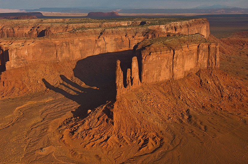 Aerial view of Navajo house at the foot of Three Sisters monoliths. Monument Valley, Arizona, USA. - Monument-Valley-Agathla-Peak-El-Capitan-Owl-Church-Rock - Mike Reyfman Photography