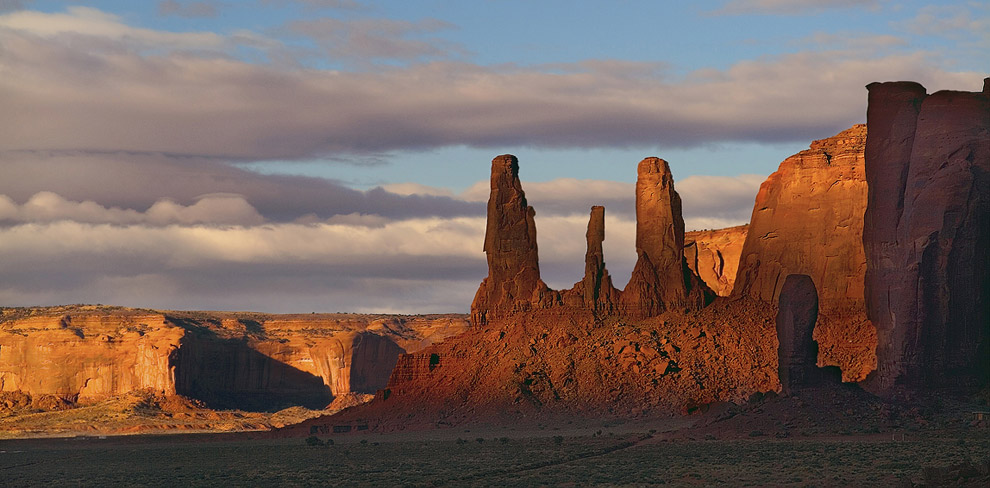 Distant view of Big Thumb and Three Sisters under stormy sky. Monument Valley, Arizona, USA. - Monument-Valley-Agathla-Peak-El-Capitan-Owl-Church-Rock - Mike Reyfman Photography