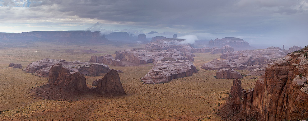 Fog rising up from the hot monoliths under the rain. Tom's Point, Hunts Mesa, Monument Valley, Arizona, USA. Panoramic. - Monument-Valley-Agathla-Peak-El-Capitan-Owl-Church-Rock - Mike Reyfman Photography