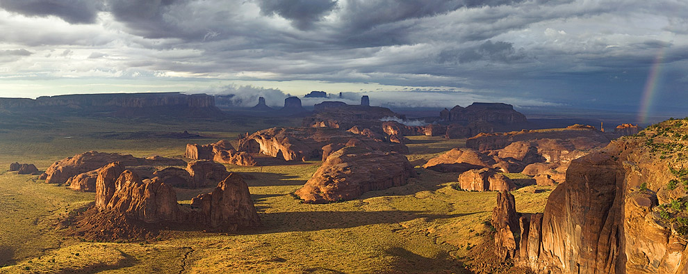 Passing storm clouds and rainbow over Monument Valley. Tom's Point, Hunts Mesa, Monument Valley, Arizona, USA. Panoramic. - Monument-Valley-Agathla-Peak-El-Capitan-Owl-Church-Rock - Mike Reyfman Photography