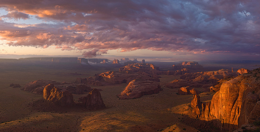 Passing storm clouds over Monument Valley at sunset. Tom's Point, Hunts Mesa, Monument Valley, Arizona, USA. Panoramic.