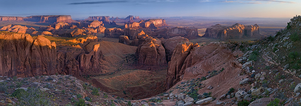 Photographer on the cliff over Monument Valley at sunrise. Hunts Mesa, Monument Valley, Arizona, USA. Panoramic. - Monument-Valley-Agathla-Peak-El-Capitan-Owl-Church-Rock - Mike Reyfman Photography