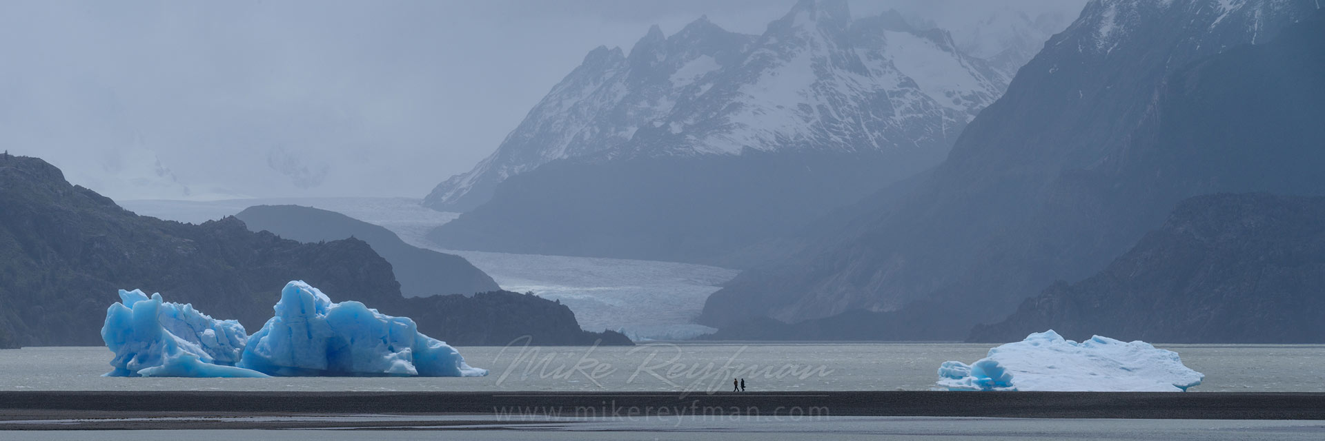 Tourists exploring icebergs in Lago Grey with Grey Glacier on the background. Torres del Paine National Park, Ultima Esperanza Province, Magallanes and Antartica Chilena Region XII, Patagonia, Chile. - Torres-Del-Paine-National-Park-Patagonia-Chile - Mike Reyfman Photography
