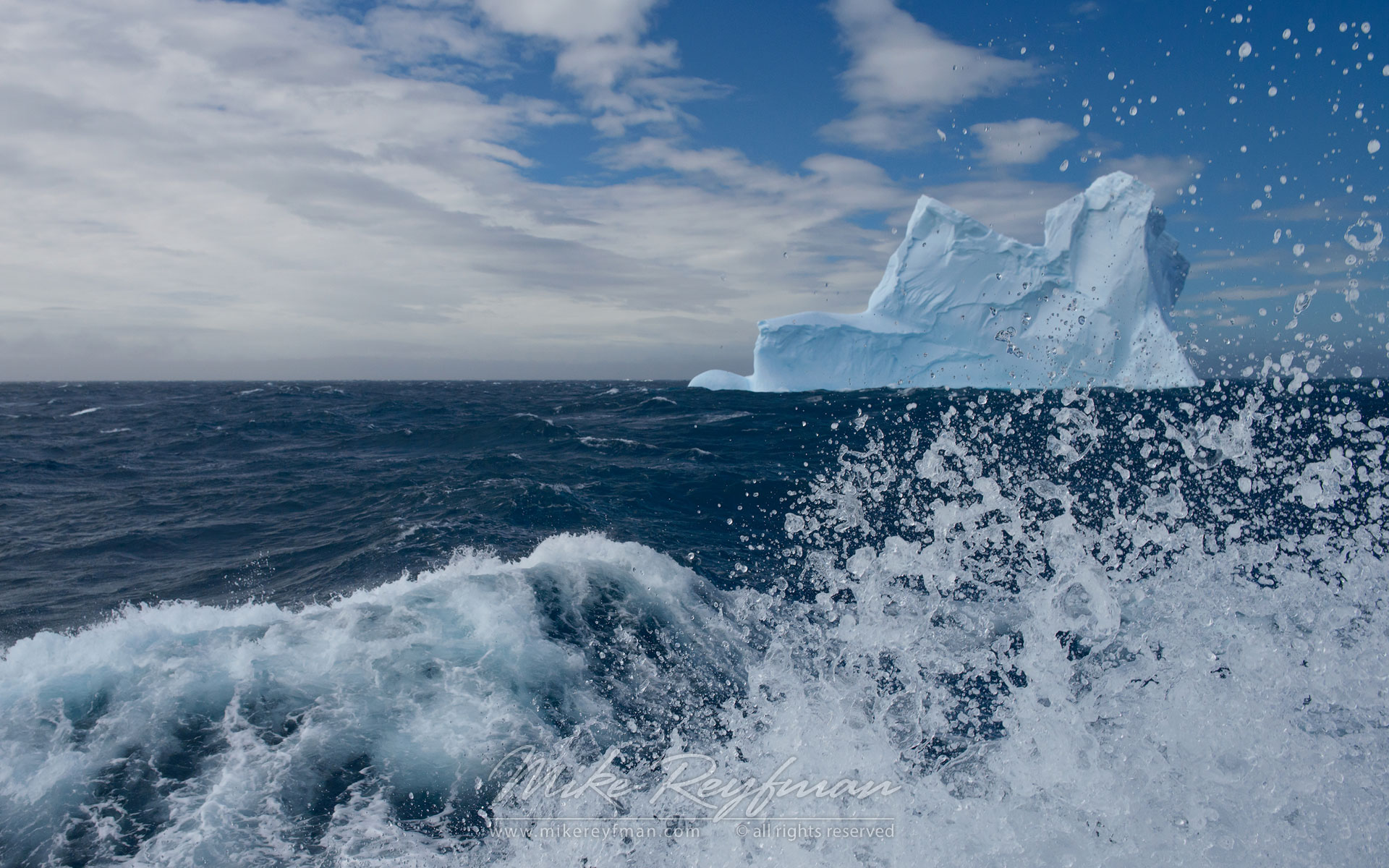 Blue iceberg seen through splashing wave. South Georgia, Sub Antarctic. - Albatrosses-Petrels-Landscapes-South-Georgia-Sub-Antarctic - Mike Reyfman Photography