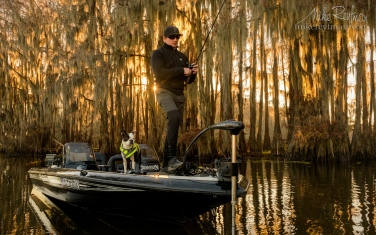 Fisherman-in-Bald-Cypress-Trees-alley.-Government-Ditch,-Lake-Caddo,-Texas,-US