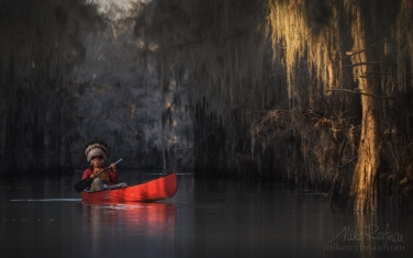 Kayaker-wearing-Native-American-Headdress-paddling-in-the-Bald-Cypress-Trees-alley.-Government-Ditch,-Lake-Caddo,-Texas,-US