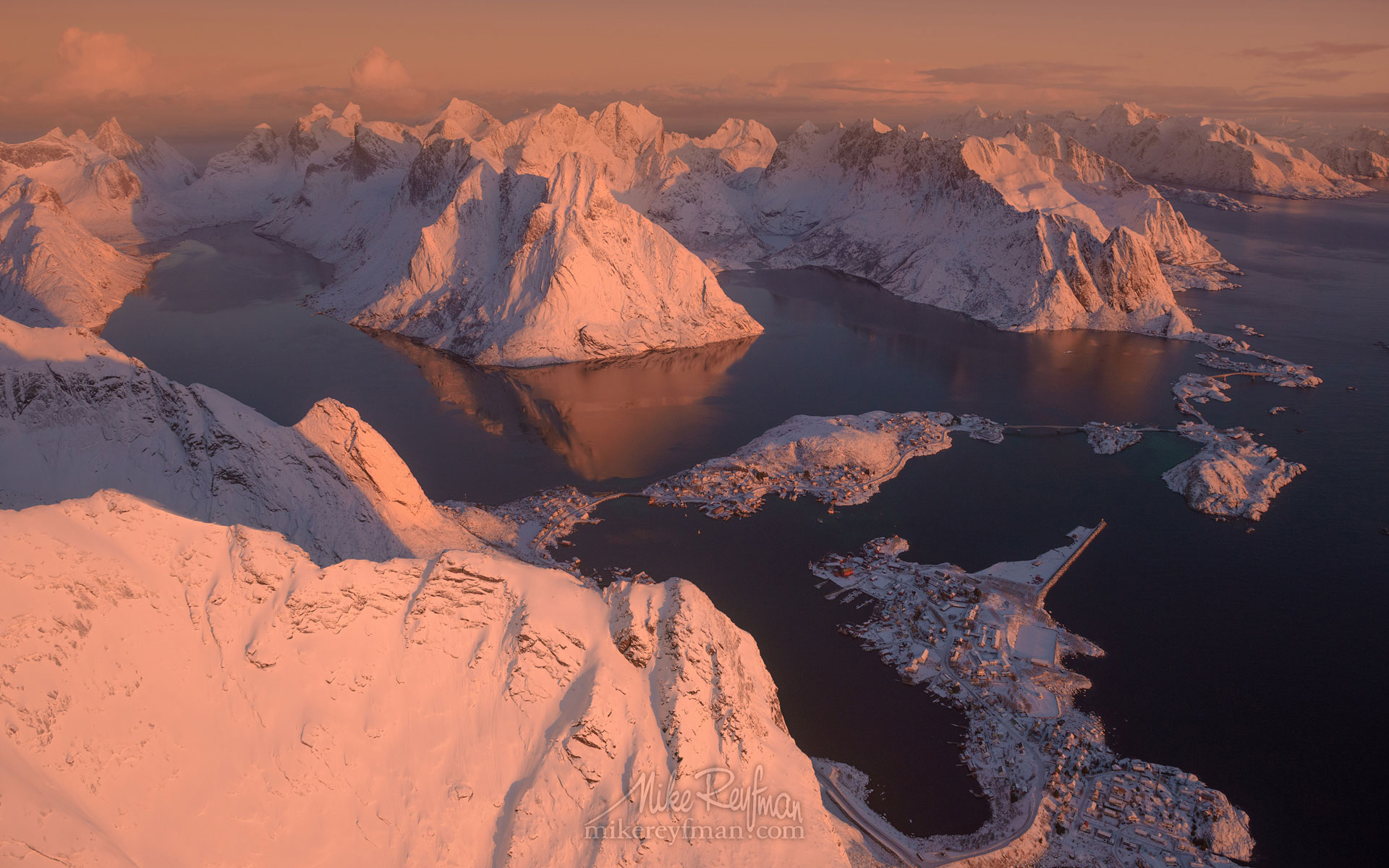 Aerial view of Lofoten archipelago, Olstinden mountain peak and fishing village of Reine at sunrise. Moskenesoya Island, Lofoten archipelago, Norway LF-MRD1E1480 - Lofoten Archipelago in Winter, Arctic Norway - Mike Reyfman Photography
