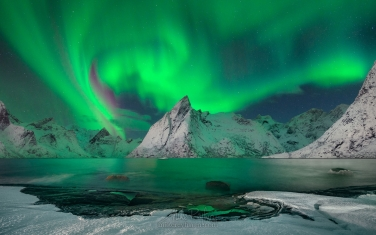 Ligt-Swirl.-Olstinden-mountain-peak-under-Aurora-Sky.-Hamnoy,-Moskenes,-Lofoten-Islands,-Norway.