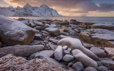 Vareid-Shoreline-and-Jagged-snow-capped-peaks-of-Flakstad-Fjord-before-sunset.-Vareid,-Flakstadoya-island,-Lofoten-archipelago,-Nordland,-Norway.