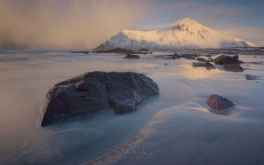 Afternoon-at-Skagsanden-beach-surrounded-by-snow-covered-mountains-reflected-in-the-cold-sea,-Flakstad,-Lofoten-Islands,-Arctic,-Norway,-Scandinavia,-Europe