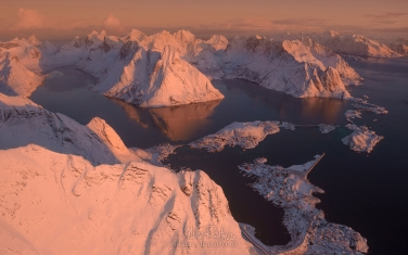 Aerial-view-of-Lofoten-archipelago,-Olstinden-mountain-peak-and-fishing-village-of-Reine-at-sunrise.-Moskenesoya-Island,-Lofoten-archipelago,-Norway