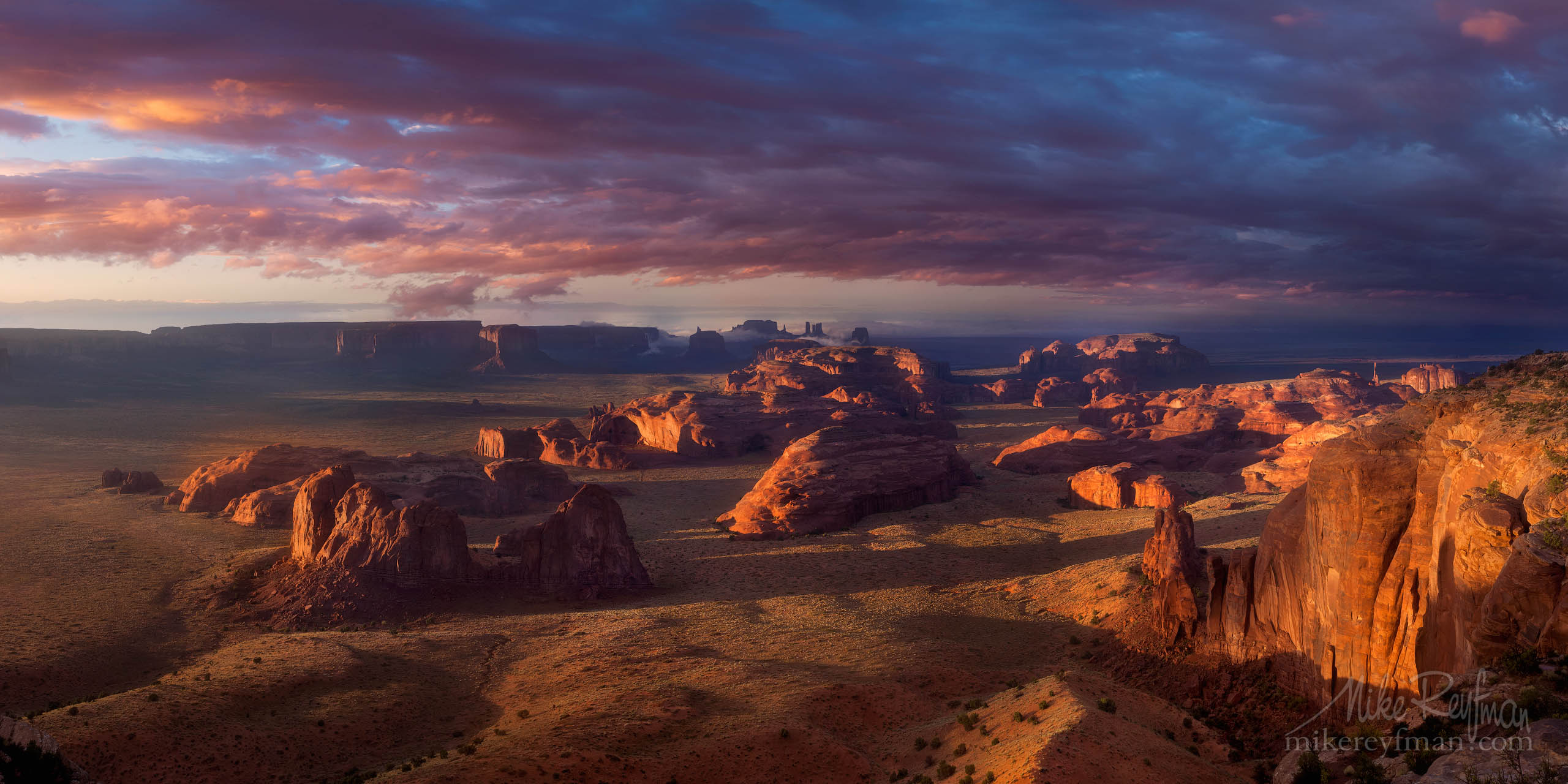 Hunts Mesa. Sunset chasing the late afternoon storm out of Monument Valley. Hunts Mesa, Monument Valley tribal Park, Arizona, USA. Panoramic P12-MR14067-69-4110-12-Pano - Selected panoramic images with 2:1 aspect ratio - Mike Reyfman Photography