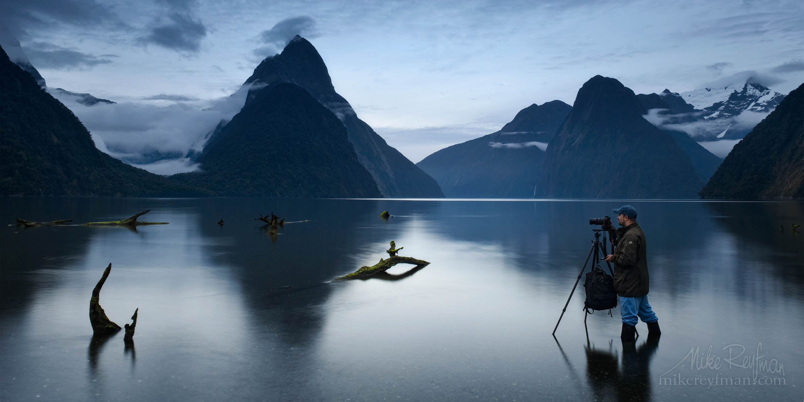Frozen. Photographer taking photos of Milford Sound at Low tide. Milford Sound, Fiordland National Park, New Zealand. P12-MRMR41708 - Selected panoramic images with 2:1 aspect ratio - Mike Reyfman Photography
