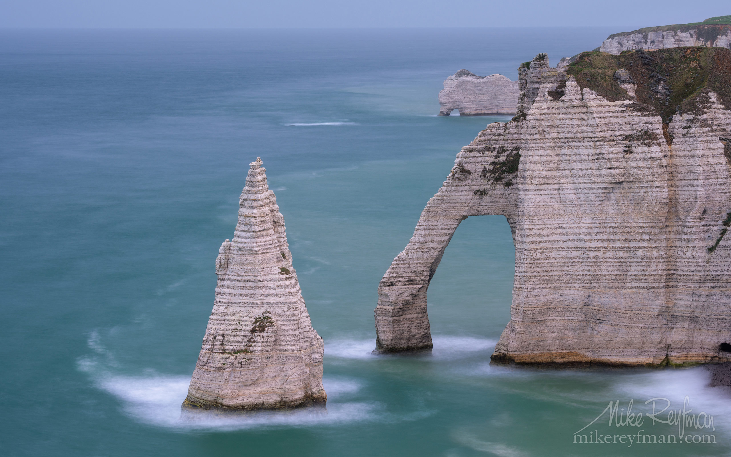 Arch Porte d'Aval and L'Aiguille - the Needle with the Porte d'Amont arch in the distance. Cote d'Albatre – The Alabaster Coast. Ertretat, Normandy, France ET1-MR50A0548 - White Chalk Cliffs and Arches of Alabaster Coast. Etretat, Upper Normandy, France - Mike Reyfman Photography