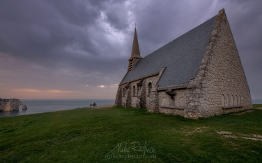 Notre-Dame-de-la-Garden-chapel-with-the-Porte-d'Aval-arch-and-L'Aiguille---the-Needle-in-the-distance.-Cote-d'Albatre-–-The-Alabaster-Coast.-Ertretat,-Normandy,-France